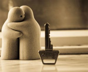Key on a table standing on its end. Behind, two cute figurines are hugging.