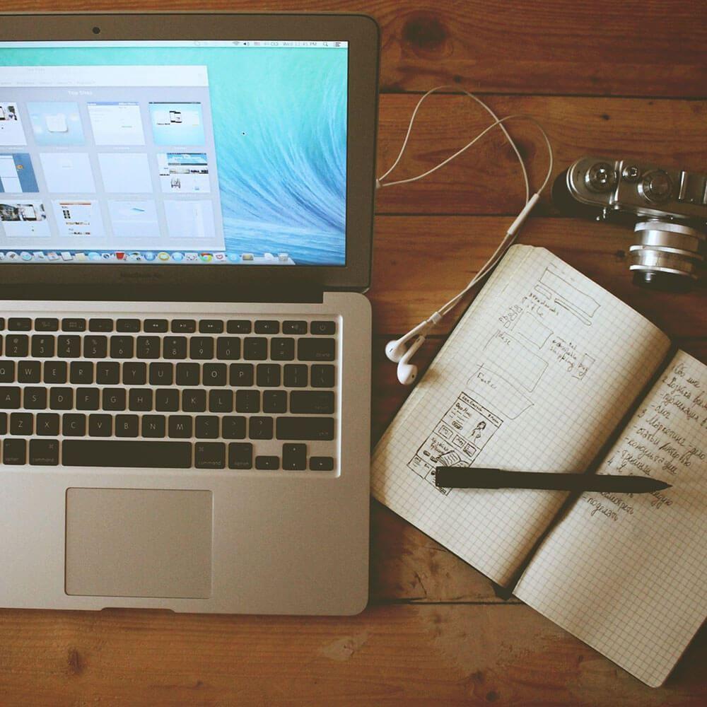 Mac, camera and notepad
