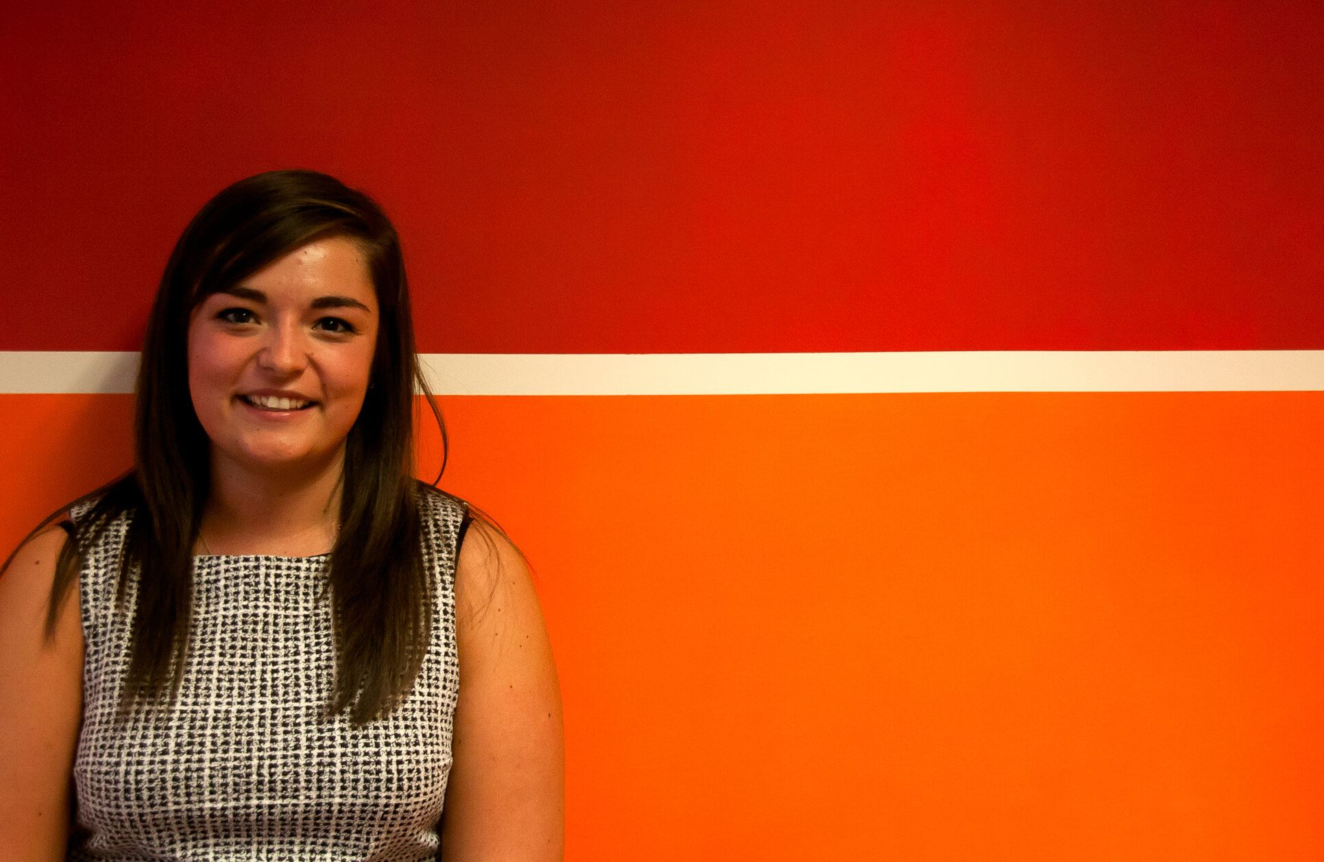 Emma looking at camera standing next to orange wall.