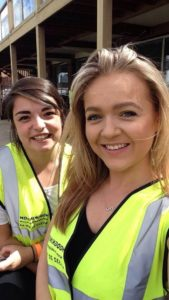 Two people posing wearing high visibility vest.