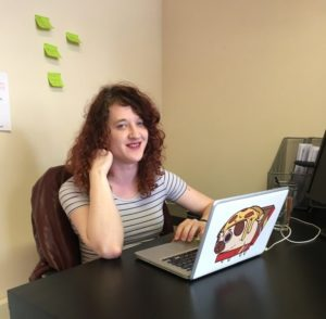 Jessica Perren sat at desk with laptop.