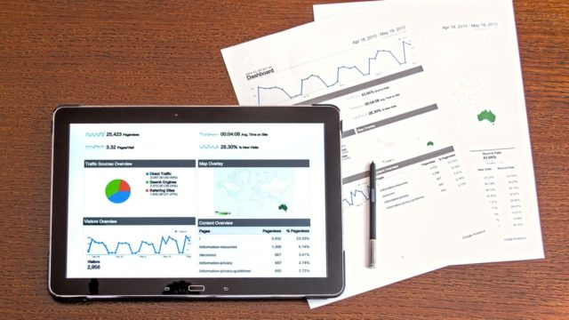 analytics dashboard displaying on an ipad with printouts of analytic reports